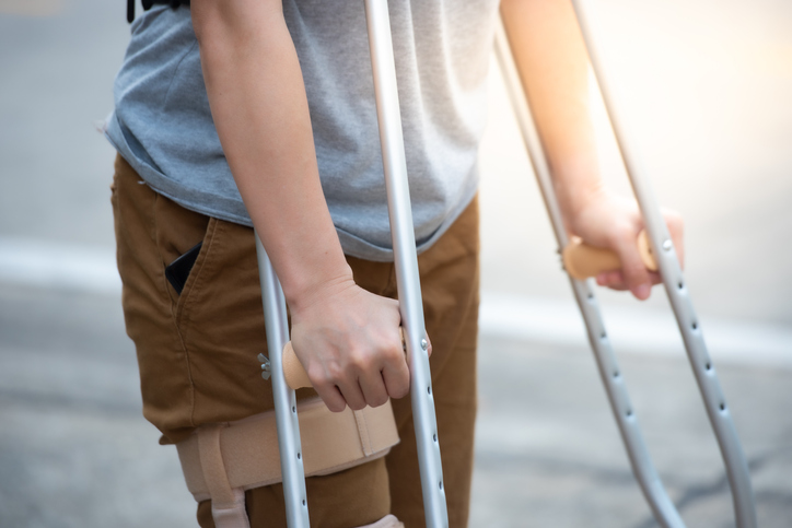 Disabled woman with crutches or walking stick or knee support standing in back side, half body.