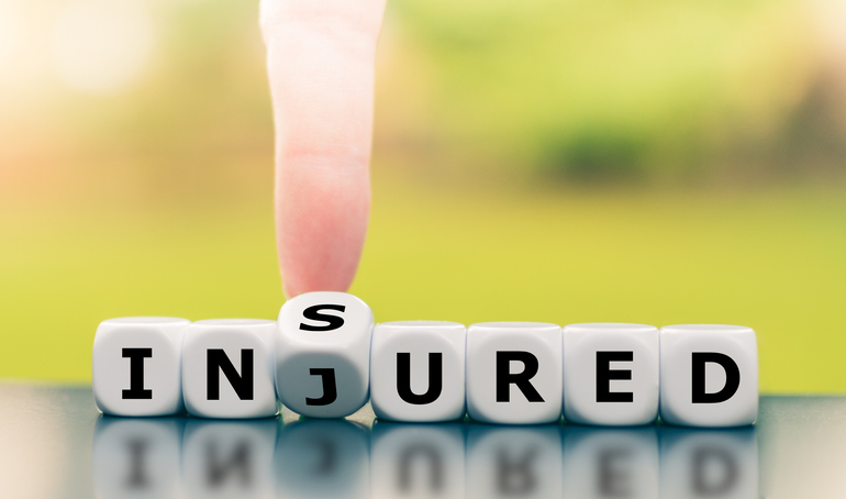 Be insured when injured. Hand turns a dice and changes the word injured to insured.