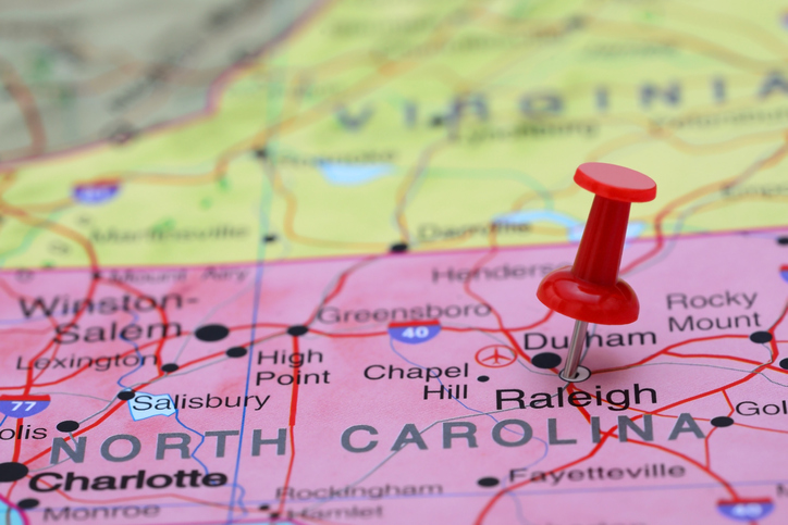 Photo of pinned Raleigh on a map of USA.
